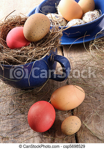 Easter eggs in blue enamel cup with straw - csp5698529