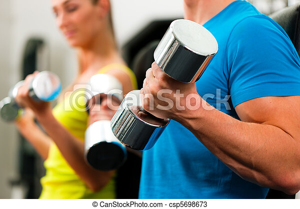 couple in gym exercising with dumbbells - csp5698673