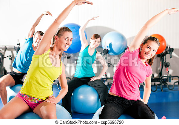 People in gym on exercise ball - csp5698720