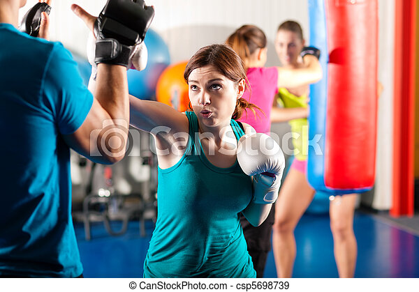 Female kick boxer with trainer in sparring - csp5698739