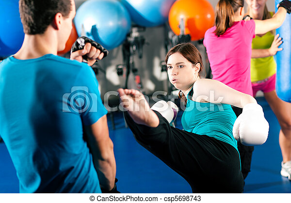 Female kick boxer with trainer in sparring - csp5698743