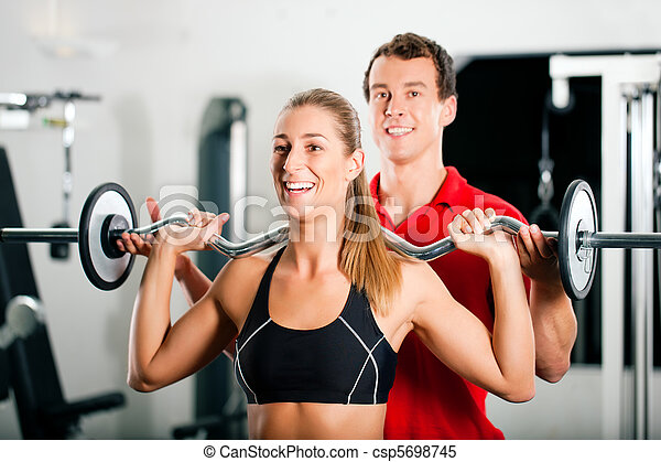 Woman with Personal Trainer in gym - csp5698745