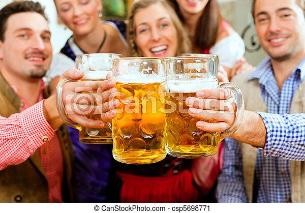 People drinking beer in Bavarian pub - csp5698771