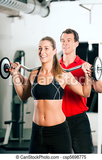 Woman with Personal Trainer in gym - csp5698775
