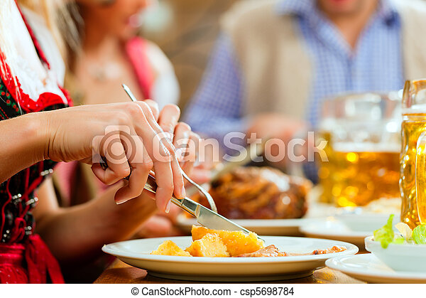 People eating roast pork in Bavarian restaurant - csp5698784