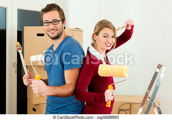 Young couple moving in a home or apartment, they are painting and doing renovation work - csp5698893