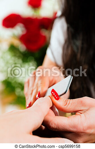 Woman in nail salon receiving manicure - csp5699158