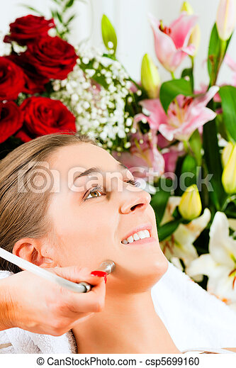 Woman in cosmetic salon receiving facial - csp5699160