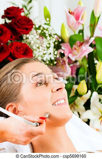 Woman in cosmetic salon receiving facial - csp5699160