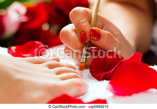 Woman in nail studio receiving pedicure - csp5699210