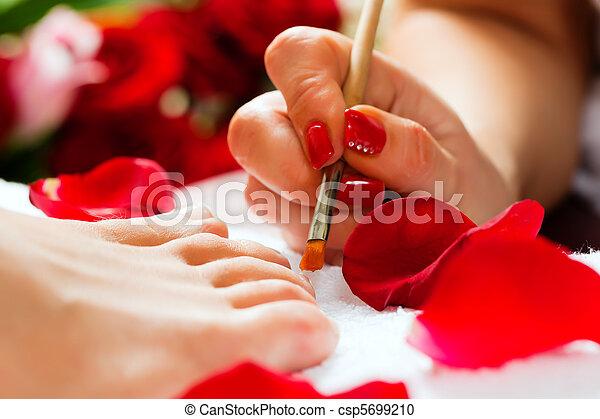 Woman in nail studio receiving pedicure - csp5699210