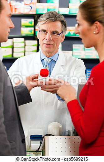 Pharmacist with customers in pharmacy - csp5699215