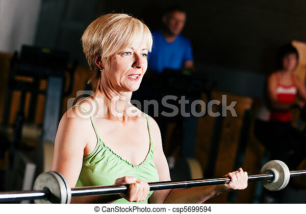 Senior Woman with barbell in gym - csp5699594