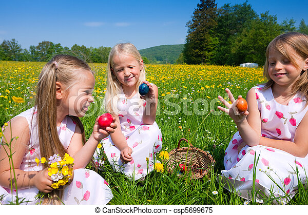 Children on Easter egg hunt with eggs - csp5699675