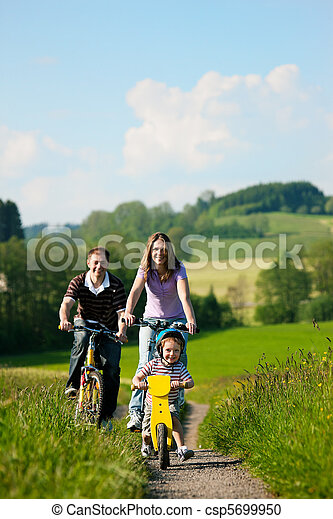 Family riding bicycles in summer - csp5699950