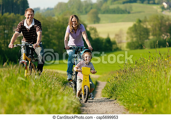 Family riding bicycles in summer - csp5699953