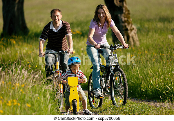 Family riding bicycles in summer - csp5700056