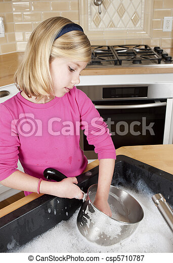 Young girl helping with cleaning by washing dishes. Girl holding cooking pot and head turned to the side. - csp5710787