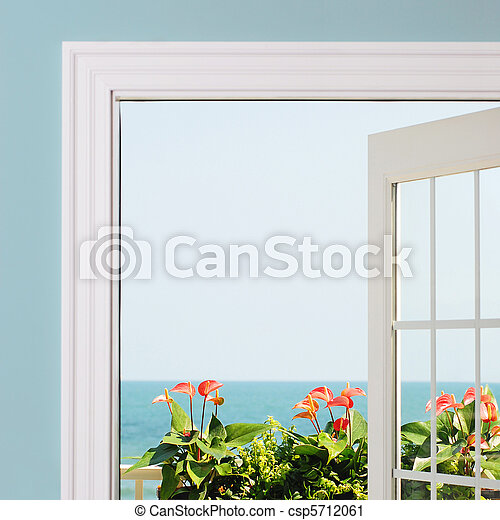 View of ocean from inside of resort / house. Anthurium blooms and green foliage in view. - csp5712061