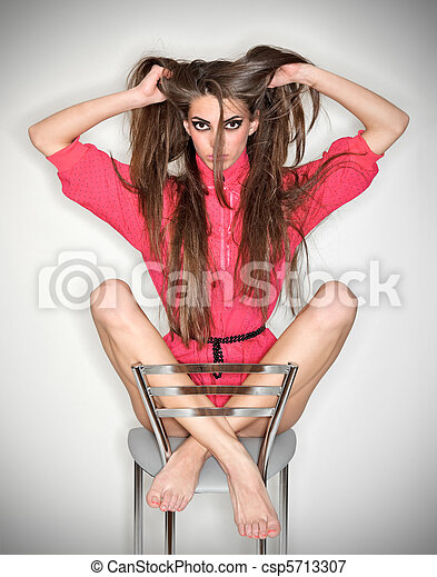 Funny confused emotion woman in pink blouse holding long tousled hairs, ring flash studio portrait on white - csp5713307