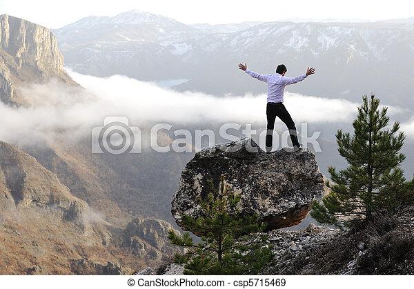 Man on top of mountain with open arms. Conceptual design. - csp5715469