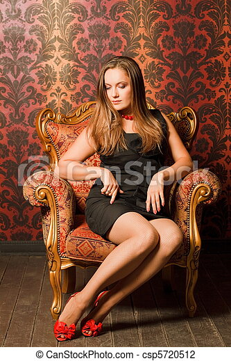 Woman in red shoes and a black dress sitting on a chair with a red-yellow wallpaper. long hair, looking down. think - csp5720512