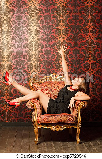 Woman in red shoes and a black dress sitting on a chair with a red-yellow wallpaper. hand is raised up. joy - csp5720546