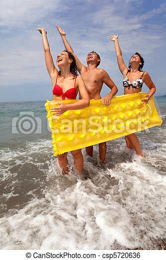 trio of young people have fun on seacoast and hold yellow inflatable mattress. youth group has rest on beach. guy and two girls stand ashore having lifted hands. - csp5720636