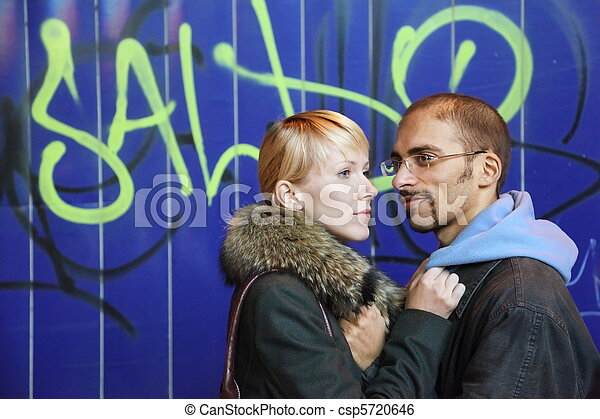 nightly street of coldly fall city. man and woman is staying near graffiti wall. - csp5720646