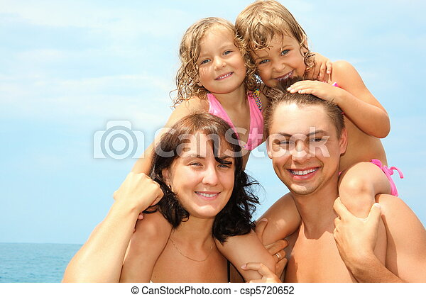 mother and father near water with two little girls sitting on their necks. they are cuddling. - csp5720652