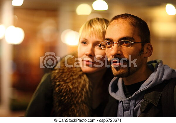 man and woman is pasearing in coldly night city. focus on man's face. - csp5720671