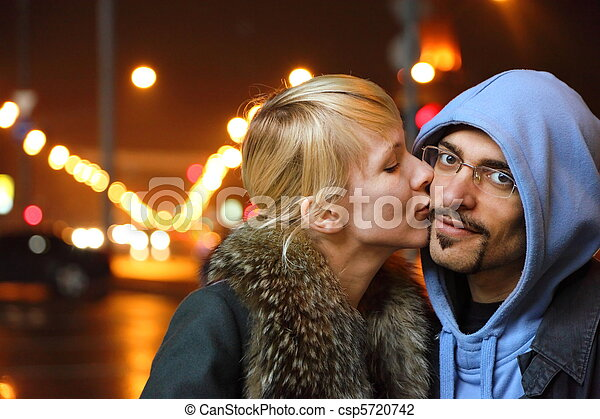 street of night coldly fall city. woman is kissing her man. focus on man's face. - csp5720742