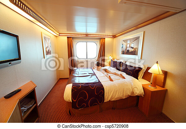 little boy lies on big double bed in ship cabin general view summer day - csp5720908