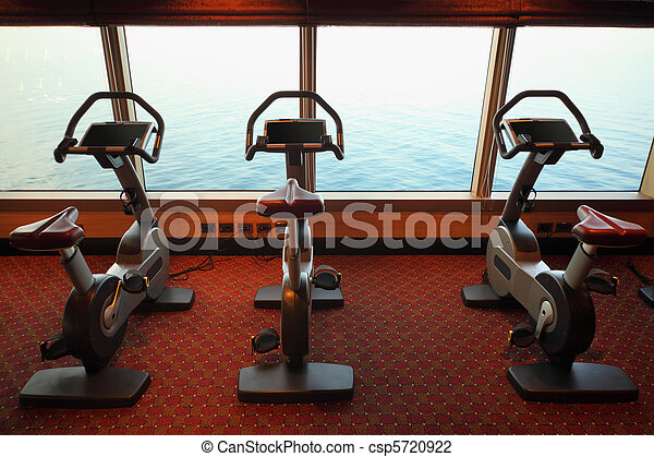 large gym hall with exercise bicycle near window with view on sea in cruise ship - csp5720922