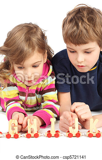 little boy and girl playing with wooden railway, lying on floor, half body, isolated on white - csp5721141