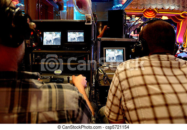 two video operators controlling camera at performance show view from back - csp5721154