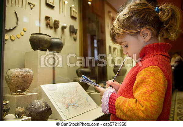 little girl writes to writing-books at excursion in historical museum near exhibits of ancient relics in glass cases  - csp5721358