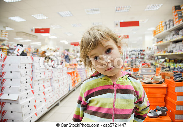 little girl in supermarket alone, chooses in department footwear  - csp5721447