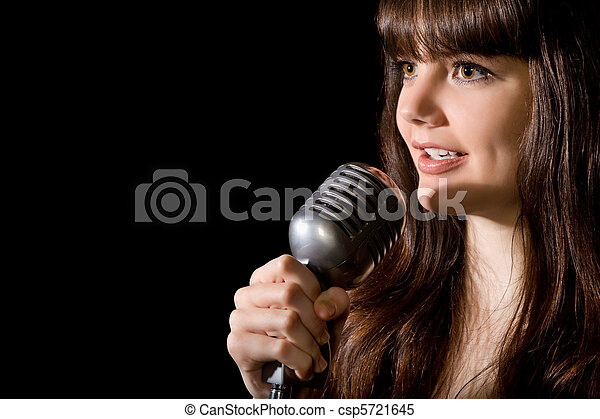 young beautiful woman sing in microphone isolated on black background - csp5721645