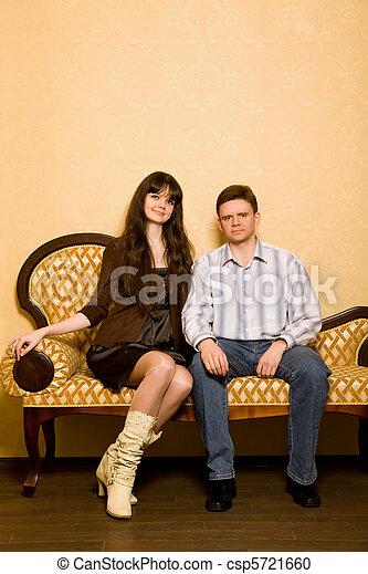 stock fotografie von junger sch ne frau junger mann sitzen sofa zimmer csp5721660. Black Bedroom Furniture Sets. Home Design Ideas
