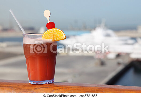 cocktail with fruits in glass on ship deck rail, port with cruise liner on background - csp5721855