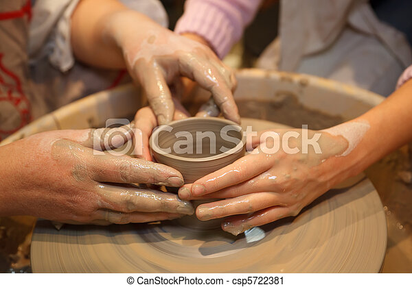 Hands of two people create pot on potter's wheel. Teaching traditional crafts. Focus on the hands. - csp5722381