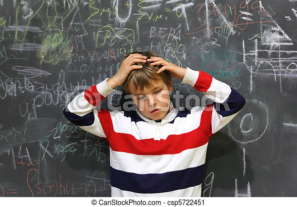 pupil standing near school board and hold on his head half body sad face - csp5722451