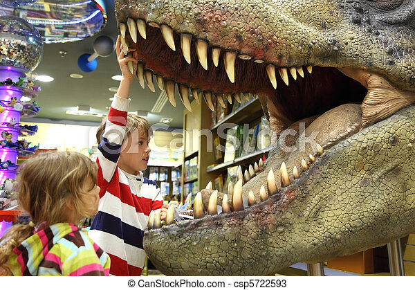 little boy and girl looking in tyrannosaurus opened mouth focus on boy side view - csp5722593