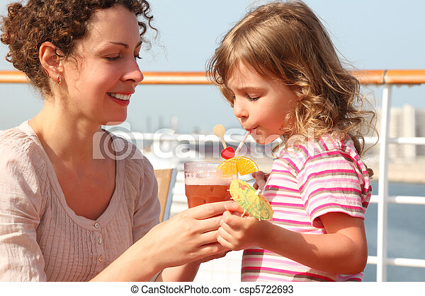 mother and daughter standing on cruise liner deck, mother holding cocktail in glass, daughter drinking it, horizontal - csp5722693