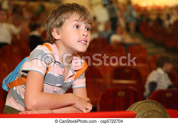 little boy in circus leans on red rail looking into the distance and waiting for performance start - csp5722704