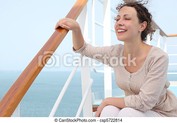 young curl woman sitting on stairs and holding for rail on cruise liner deck, looking left and smiling - csp5722814