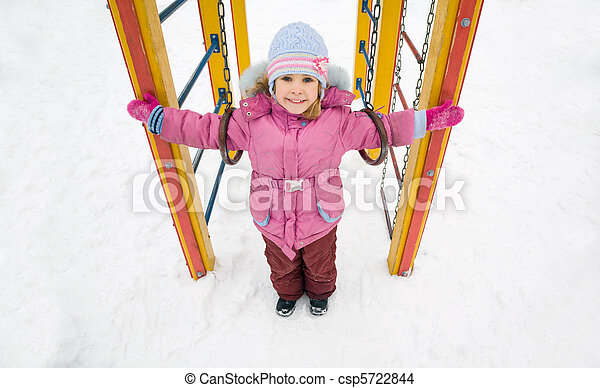 little pretty smiling girl in pink jacket on playground in winter, girl placed hands in sides - csp5722844