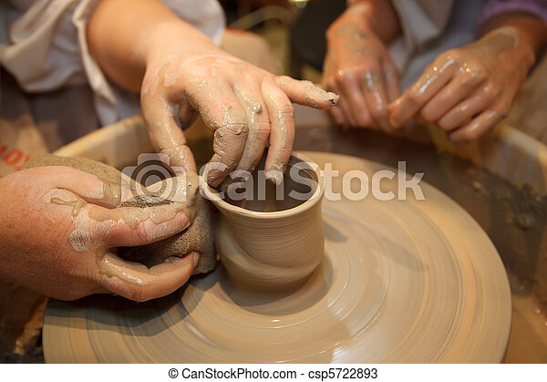 Hands of master creating pot on potter's wheel. Traditional craft. Focus on the hands. - csp5722893