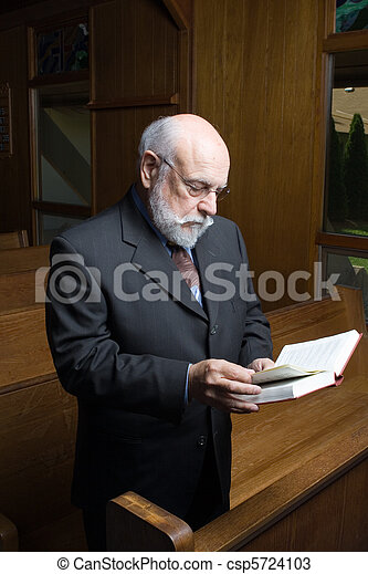 Standing Senior Caucasian Man Reading Hymnal In Church Pew - csp5724103